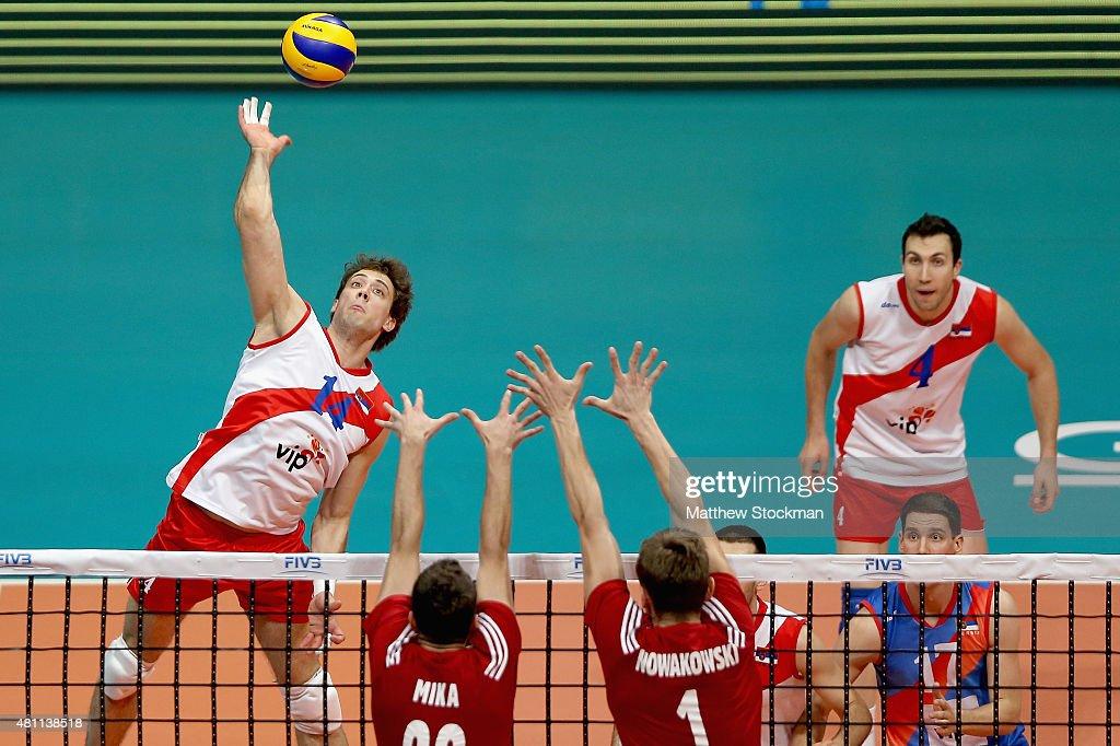 Aleksandar Atanasijevic of Serbia spikes the ball against (L-R) Mateusz Mika and Piotr Nowakowski of Poland during the FIVB World League Group 1 Finals match between Serbia and Poland at Maracanazinho Gymnasium on July 17, 2015 in Rio de Janeiro, Brazil.