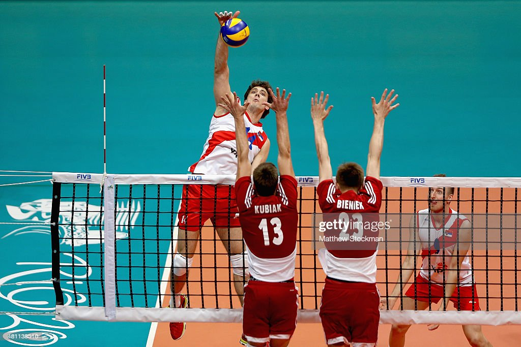 Aleksandar Atanasijevic of Serbia spikes the ball against (L-R) Michal Kubiak and Mateusz Bieniek of Poland during the FIVB World League Group 1 Finals match between Serbia and Poland at Maracanazinho Gymnasium on July 17, 2015 in Rio de Janeiro, Brazil.