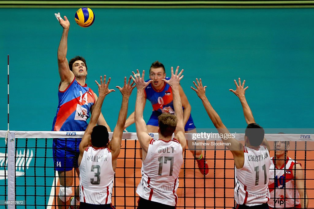 Aleksandar Atanasijevic of Serbia spikes the ball against (L-R) Taylor Sander, Maxwell Holt and Micah Christenson of the United States during the FIVB World League Group 1 Finals semi-final match between the United States and Serbia at Maracanazinho on July 18, 2015 in Rio de Janeiro, Brazil.