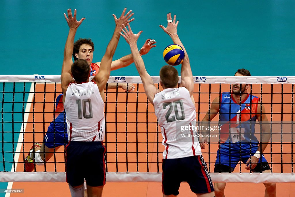 Aleksandar Atanasijevic of Serbia spikes the ball against (L-R) Thomas Jaeschke and David Smith of the United States during the FIVB World League Group 1 Finals semi-final match between the United States and Serbia at Maracanazinho on July 18, 2015 in Rio de Janeiro, Brazil.