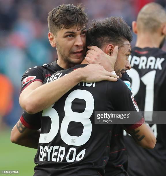 Aleksandar Dragovic of Leverkusen shakes hands with Karim Bellarabi during the Bundesliga match between Bayer 04 Leverkusen and VfL Wolfsburg at...