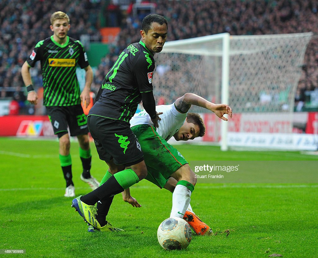 Aleksandar Ignjovski of Bremen is challenged by Raffael Caetano de Araújo of Gladbach during the Bundesliga match between Werder Bremen and Borussia Moenchengladbach at Weserstadion on February 15, 2014 in Bremen, Germany.