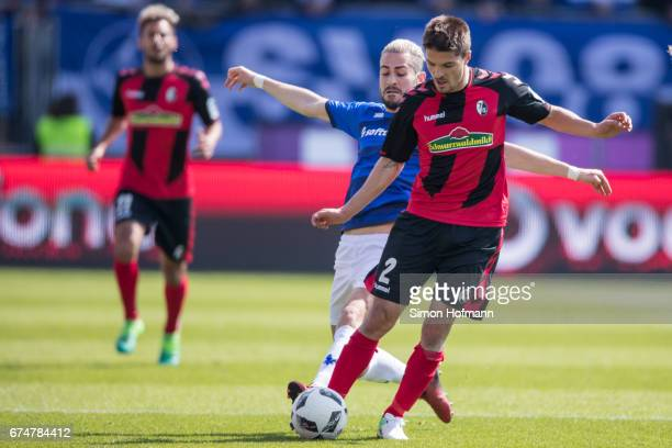 Aleksandar Ignjovski of Freiburg is challenged by Mario Vrancic of Darmstadt during the Bundesliga match between SV Darmstadt 98 and SC Freiburg at...