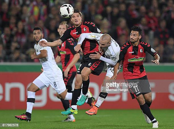 Aleksandar Ignjovski of Freiburg Korbinian Vollmann of Sandhausen and Onur Bulut of Freiburg compete for the ball during the DFB Cup match between SC...