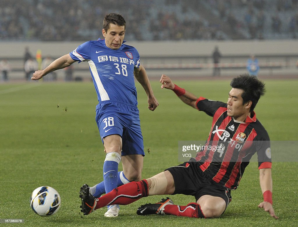 Aleksandar Jevtic #38 of Jiangsu Sainty and Kim Ju-Young #4 of FC Seoul battle for the ball during the AFC Champions League match between Jiangsu Sainty and FC Seoul at Nanjing Olympic Sports Center Stadium on April 24, 2013 in Nanjing, China.