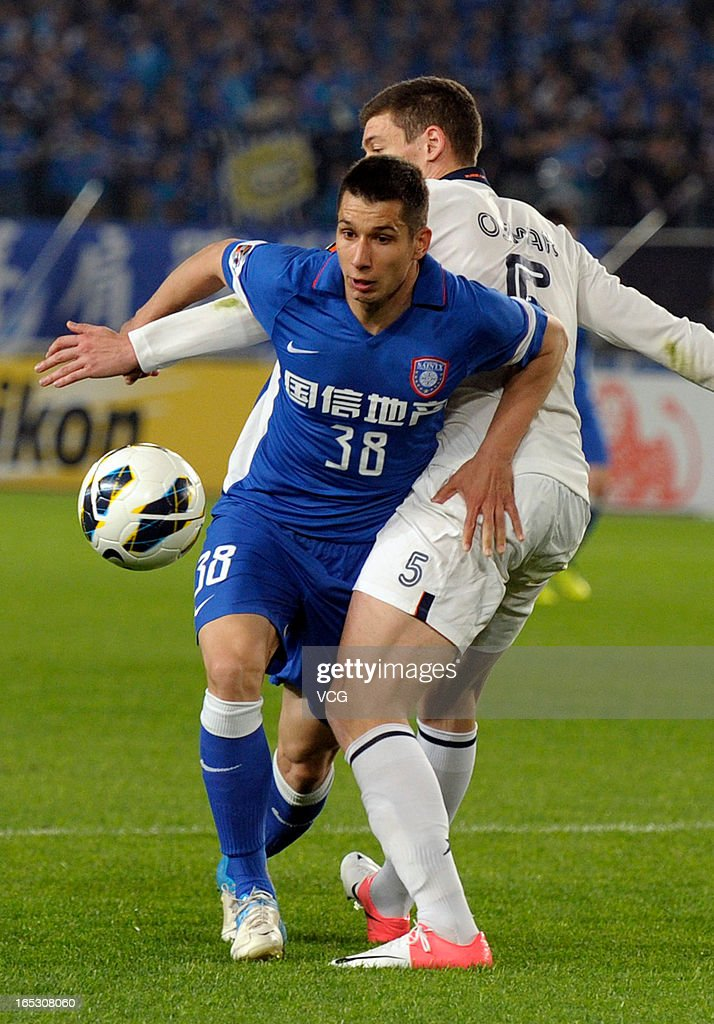 Aleksandar Jevtic #38 of Jiangsu Sainty and Osmar Barba #5 of Buriram United battle for the ball during the AFC Champions League match between Jiangsu Sainty and Buriram United at Nanjing Olympic Sports Center Stadium on April 2, 2013 in Nanjing, China.