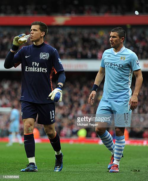 Aleksandar Kolarov of Man City looks on as Wojciech Szczesny of Arsenal pretends to drink a bottle of beer that was thrown onto the pitch during the...
