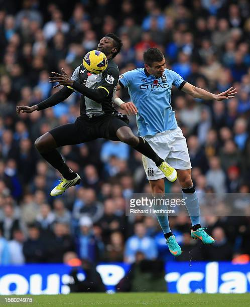 Aleksandar Kolarov of Manchester City competes in the air with Emmanuel Adebayor of Tottenham Hotspur during the Barclays Premier League match...