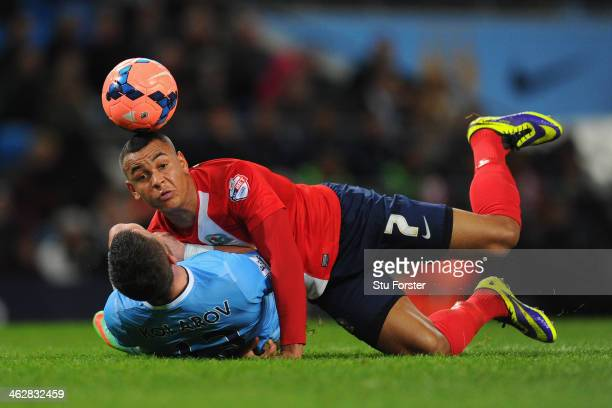 Aleksandar Kolarov of Manchester City tangles with Joshua King of Blackburn Rovers during the Budweiser FA Cup Third Round Replay match between...