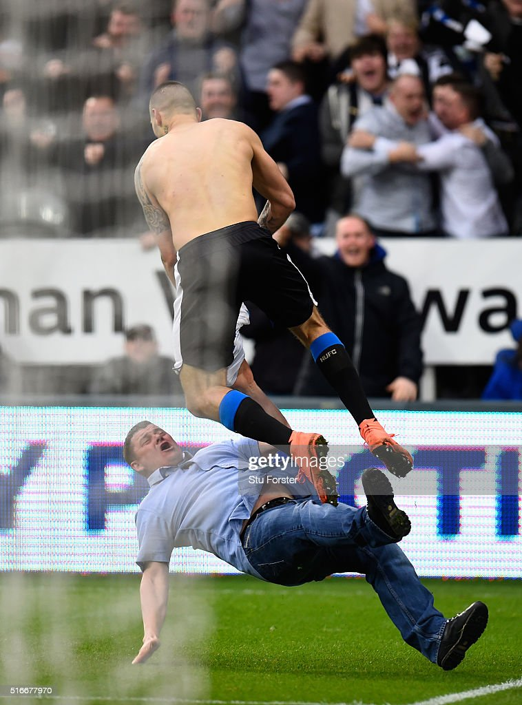 Aleksandar Mitrovic of Newcastle United collides with a fan as he celebrates scoring their first and equalising goal during the Barclays Premier League match between Newcastle United and Sunderland at St James' Park on March 20, 2016 in Newcastle upon Tyne, United Kingdom.