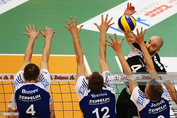 Aleksandar Spirovski of Berlin tries to pass the block of Valentin Bratoev Victor Yosifov and Nikola Jovovic of Friedrichshafen during game four of...