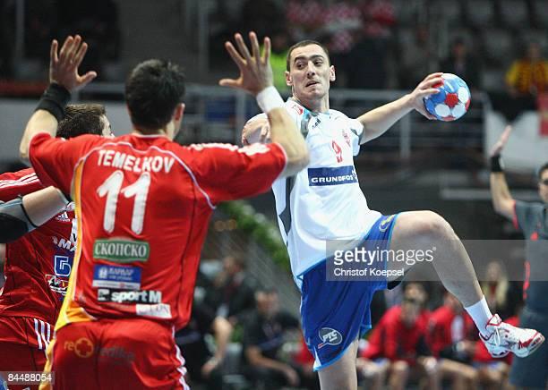 Aleksandar Stojanovic of Serbia throws the ball and Vladimir Temelkov of Macedonia blocks him during the Men's World Handball Championships main...