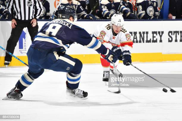 Aleksander Barkov of the Florida Panthers and Zach Werenski of the Columbus Blue Jackets battle for control of the puck during the first period on...