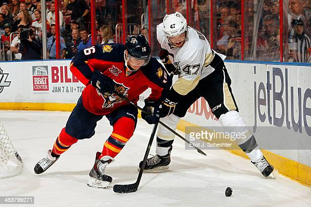 Aleksander Barkov of the Florida Panthers crosses sticks with Simon Despres of the Pittsburgh Penguins at the BBT Center on November 30 2013 in...
