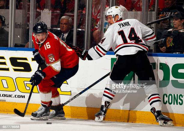 Aleksander Barkov of the Florida Panthers digs the puck out from the boards against Richard Panik of the Chicago Blackhawks at the BBT Center on...