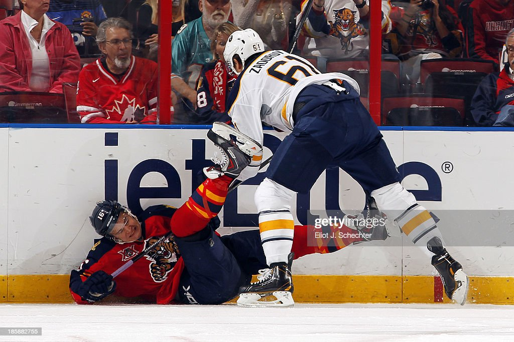 Aleksander Barkov #16 of the Florida Panthers is checked into the boards by Nikita Zadorov #61 of the Buffalo Sabres at the BB&T Center on October 25, 2013 in Sunrise, Florida.
