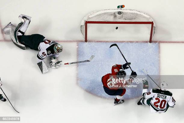 Aleksander Barkov of the Florida Panthers scores against Goaltender Devan Dubnyk and Ryan Suter of the Minnesota Wild at the BBT Center on March 10...