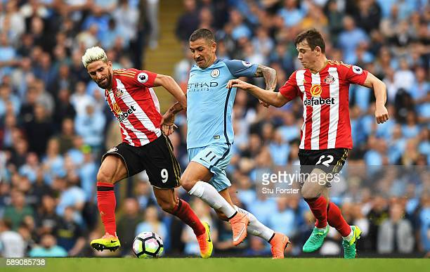Aleksander Kolorov of Manchester City battle for possession with Fabio Borini of Sunderland and Donald Love of Sunderland during the Premier League...