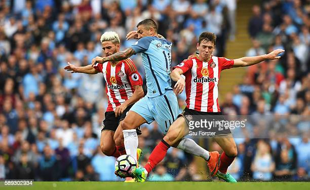 Aleksander Kolorov of Manchester City is challegned by Sunderland duo Fabio Borini of Sunderland and Donald Love of Sunderland during the Premier...