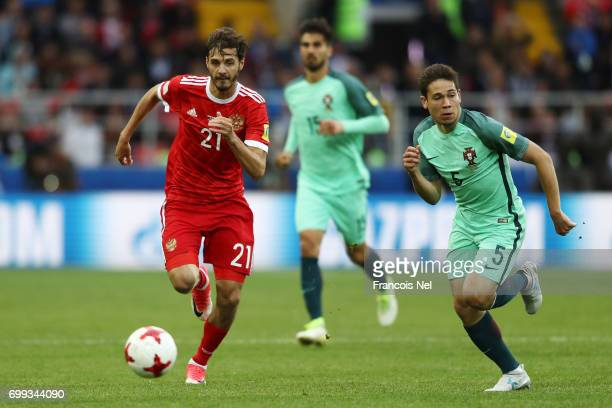 Aleksandr Erokhin of Russia attempts to take the ball past Raphael Guerreiro of Portugal during the FIFA Confederations Cup Russia 2017 Group A match...