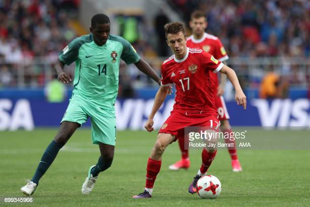 Aleksandr Golovin of Russia competes with William Carvalho of Portugal during the FIFA Confederations Cup Russia 2017 Group A match between Russia...