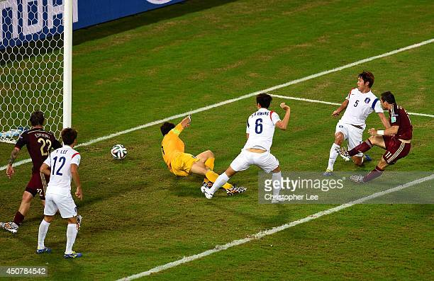 Aleksandr Kerzhakov of Russia shoots and scores his team's first goal past goalkeeper Jung SungRyong of South Korea during the 2014 FIFA World Cup...