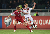 Aleksandr Kobakhidze of Georgia and Jonas Hector of Germany compete for the ball during the EURO 2016 Group D Qualifier match between Georgia and...