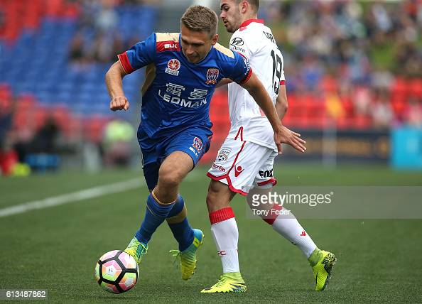 Aleksandr Kokko of the Jets contests te ball with Benjamin Garuccio of Adelaide during the round one ALeague match between the Newcastle Jets and...