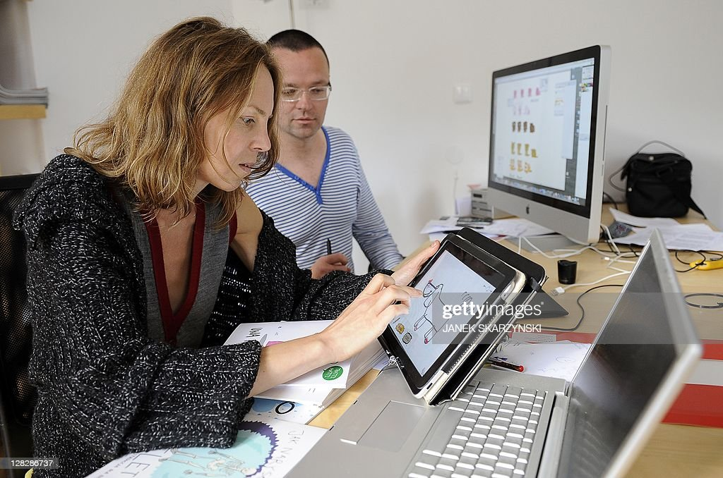 Aleksandra Szkoda shows shows an iPad application 'How to draw a dog' next to her partner Radek Zabinski in their office in Warsaw on September 27, 2011. AFP PHOTO / JANEK SKARZYNSKI