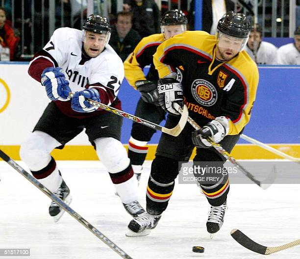 Aleksandrs Semjonovs from Latvia hooks Mark Mackay from Germany during the first period in the preliminary round of mens ice hockey at the XIX Winter...