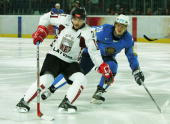 Aleksandrs Semjonovs of Latvia controls the puck away from Andrey Savenkov of Kazakhstan during the men's ice hockey Preliminary Round Group B match...