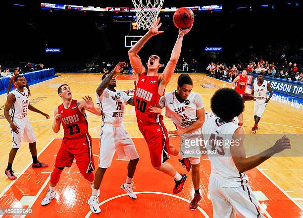 Aleksej Rostov of the Western Kentucky Hilltoppers attempts a shot between Isaiah Miles and Javon Baumann of the Saint Joseph's Hawks in the first...