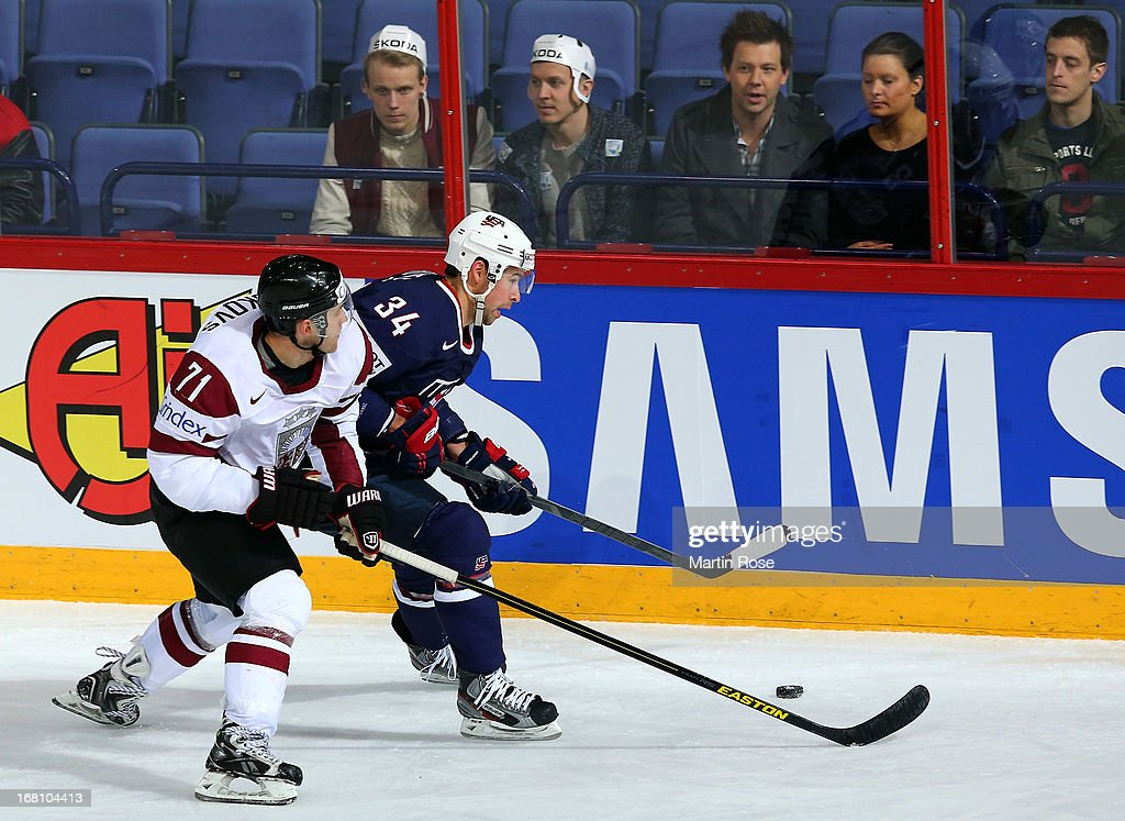Aleksejs Sirokovs (L) of Latvia and Chris Butler (R) of USA battle for the puck during the IIHF World Championship group H match between Latvia and USA at Hartwall Areena on May 5, 2013 in Helsinki, Finland.