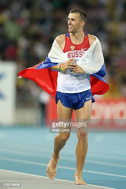 Aleksey Dmitrik of Russia celebrates with his country's flag after claiming silver in the men's high jump final during day six of the 13th IAAF World...