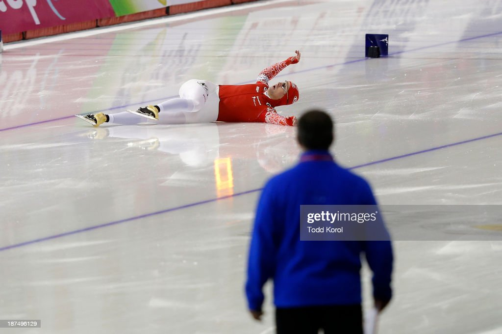 Aleksey Yesin of Russia slides down the ice as he fell on the finish line in the men's 1000 meter race during the ISU World Cup Speed Skating event November 9, 2013 in Calgary, Alberta, Canada.