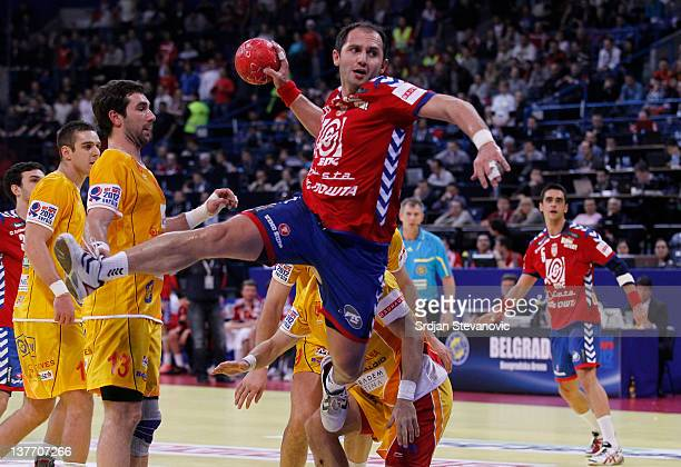 Alem Toskic of Serbia jumps to score past Filip Mirkulovski of Macedonia during the Men's European Handball Championship 2012 second round group one...
