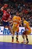 Alem Toskic of Serbia scores a goal against Filip Mirkulovski and Bransilav Angelovski of Macedonia during the Men's European Handball Championship...