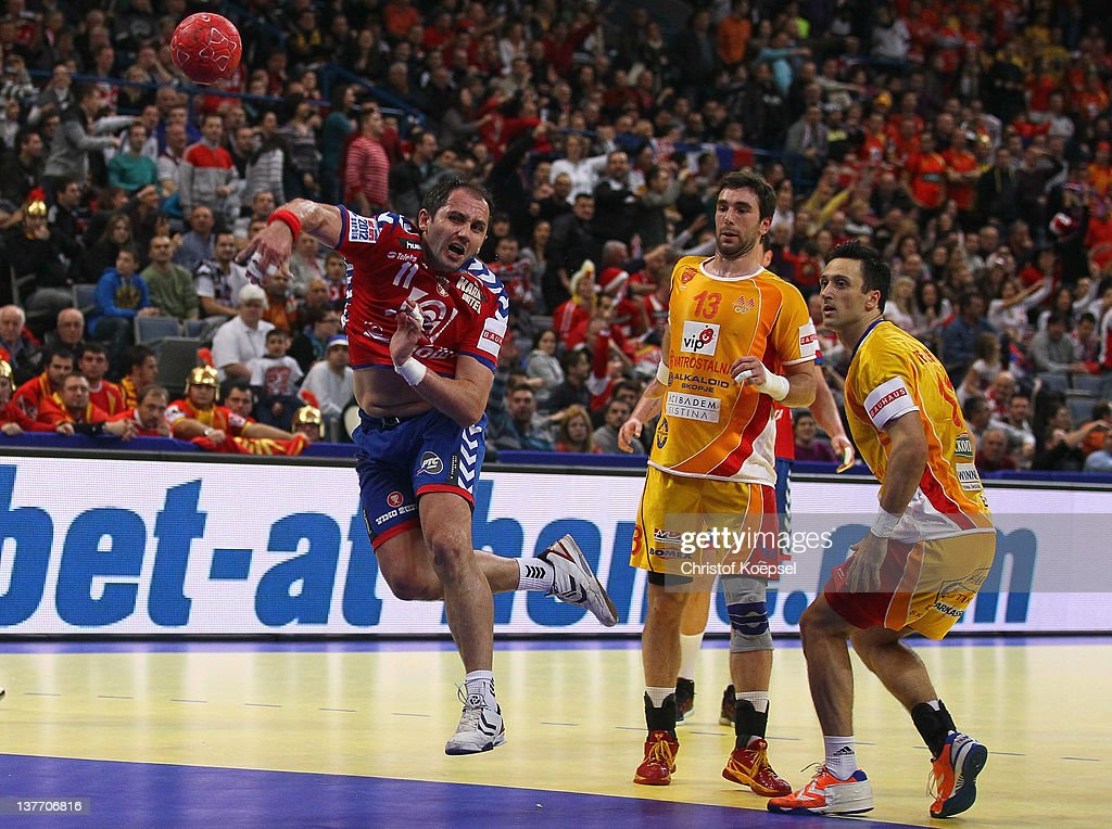 Alem Toskic of Serbia (L) scores a goal against Filip Mirkulovski (C) and Bransilav Angelovski (R) of Macedonia during the Men's European Handball Championship second round group one match between Serbia and Macedonia at Beogradska Arena on January 25, 2012 in Belgrade, Serbia.