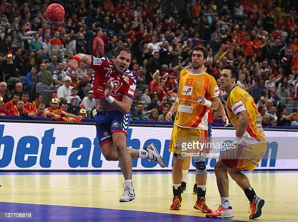 Alem Toskic of Serbia scores a goal against Filip Mirkulovski and Bransilav Angelovski of Macedonia during the Men's European Handball Championship...