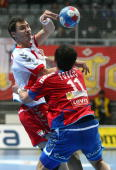 Alem Toskic of Serbia tackles Krzystof Lijewski of Poland during the Men's World Handball Championships main round match group two between Serbia and...
