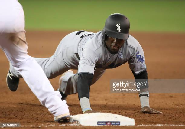 Alen Hanson of the Chicago White Sox dives back to first base safely on a pickoff attempt in the eighth inning during MLB game action against the...