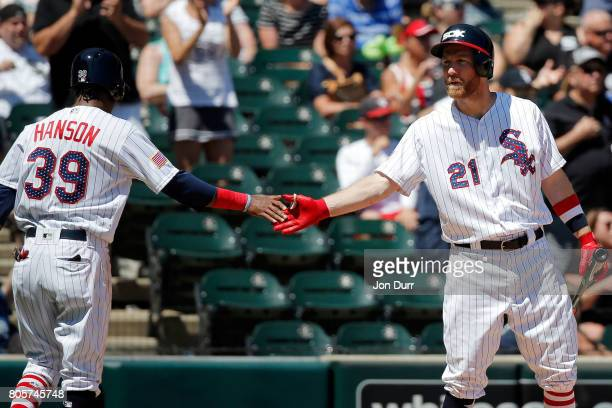 Alen Hanson of the Chicago White Sox high fives Todd Frazier after scoring against the Texas Rangers on an RBI double hit by Jose Abreu during the...