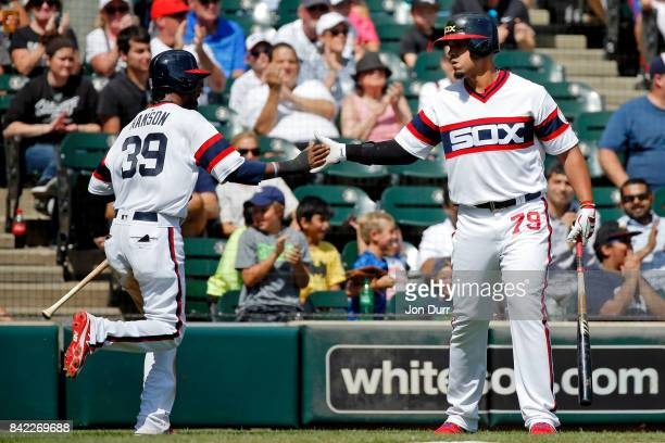Alen Hanson of the Chicago White Sox is congratulated by Jose Abreu after scoring on an RBI single hit by Tim Anderson during the third inning at...