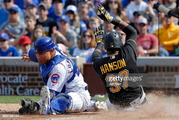 Alen Hanson of the Pittsburgh Pirates scores as Willson Contreras of the Chicago Cubs is unable to keep his foot on home plate during the eighth...