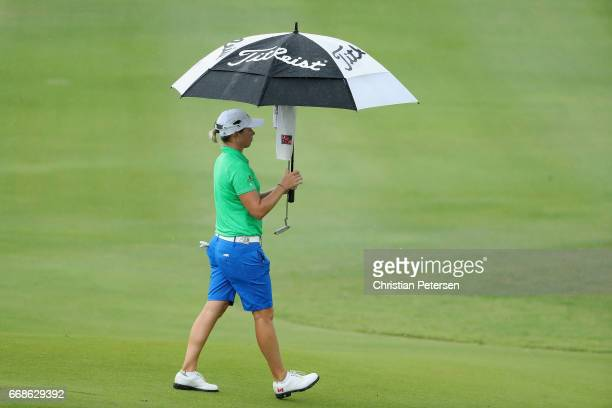 Alena Sharp of Canada walks off the second green under an umbrella during a weather delay in the third round of the LPGA LOTTE Championship Presented...