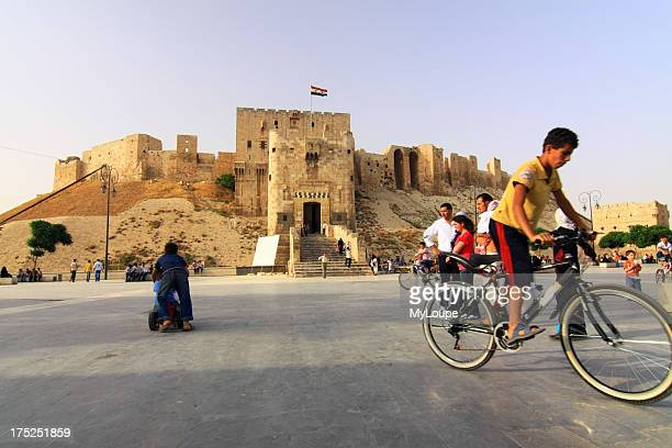 Aleppo Citadel square people bicycle Syria