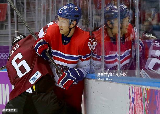 Ales Hemsky of Czech Republic is pushed into the boards by Arvids Rekis of Latvia in the second period during the Men's Ice Hockey Preliminary Round...
