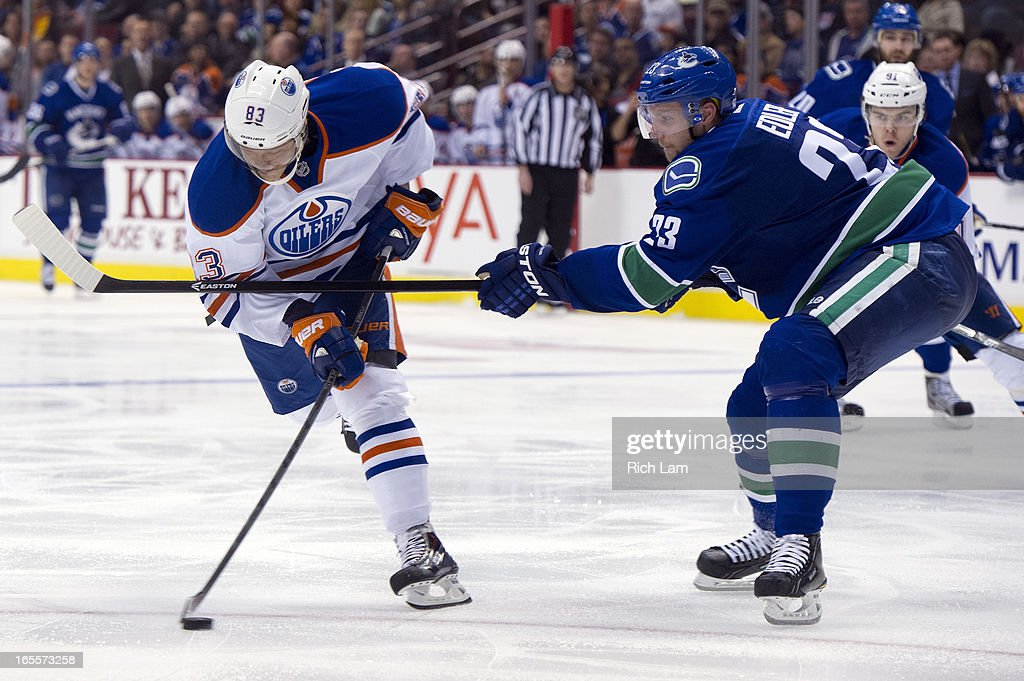 <a gi-track='captionPersonalityLinkClicked' href=/galleries/search?phrase=Ales+Hemsky&family=editorial&specificpeople=202828 ng-click='$event.stopPropagation()'>Ales Hemsky</a> #83 of the Edmonton Oilers gets slashed by <a gi-track='captionPersonalityLinkClicked' href=/galleries/search?phrase=Alexander+Edler&family=editorial&specificpeople=882987 ng-click='$event.stopPropagation()'>Alexander Edler</a> #23 of the Vancouver Canucks as he tries to get a shot on net during third period of NHL action on April 04, 2013 at Rogers Arena in Vancouver, British Columbia, Canada.