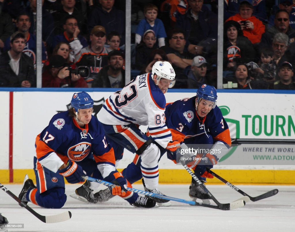 Ales Hemsky #83 of the Edmonton Oilers tries to move the puck around Matt Martin #17 (L) and Travis Hamonic #3 (R) of the New York Islanders at the Nassau Veterans Memorial Coliseum on December 31, 2011 in Uniondale, New York.