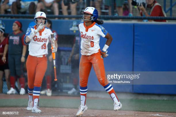 Aleshia Ocasio of the University of Florida jumps after successfully sliding into home plate during the Division I Women's Softball Championship held...